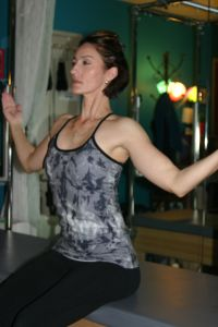 Blooming Flower - Step 3 Exhale-Release hands from head and float arms down keeping shoulders open and elbows forward. You should feel your shoulder blades (scapula) against your back.